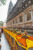 Flowers in front of walls of Mahabodhi Temple. Garlands with flowers and festive bouquets at Mahabodhi Temple, in commemoration of day of an enlightenment of Stock Images