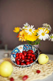 Flowers and fruits. On the table is a vase of flowers lie close dogwood fruits and apples Royalty Free Stock Image