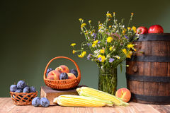 Flowers from the garden, fruit and wooden barrel Royalty Free Stock Photo