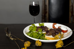 Flowers And Garnish. Yellow flowers in focus and garnish with a glass of red wine in the background, studio shot royalty free stock photo