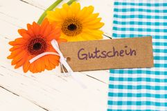 Flowers and gift card with german word, Gutschein, means voucher or coupon for Father`s day or Birthday. Yellow and orange flower gift with tag with german word Royalty Free Stock Photo