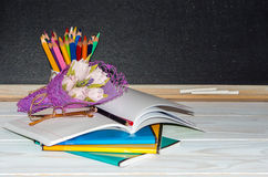 Flowers and gift; copybooks on the teacher's desk. Stock Photos