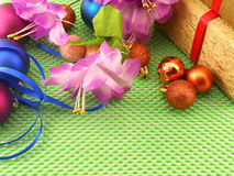 Flowers, gifts and Christmas balls on green background Royalty Free Stock Photography