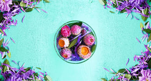 Flowers in a glass in the middle of the table. Around scattered flower petals Royalty Free Stock Images