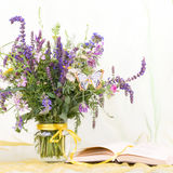 flowers in a glass vase with book Royalty Free Stock Image