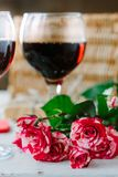 Flowers and glasses of wine on celebration of Valentine's day.  stock image