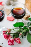 Flowers and glasses of wine on celebration of Valentine\'s day.  royalty free stock image