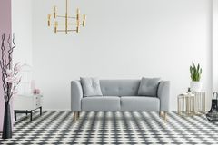 Flowers and gold chandelier in spacious living room interior wit stock photo