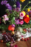 Flowers and grapes on a wooden table - elaborate Thanksgiving harvest scene. Luxurious still life of fruit, flowers and vegetables. Featuring artichoke, tulips Stock Images
