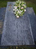 Flowers on a grave. Bouquet of flowers on a gravestone at a graveyard Stock Photo