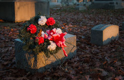 Flowers on a grave at sunset. Somber shot of red and white flowers on a tombstone in a cemetery in late afternoon Stock Image