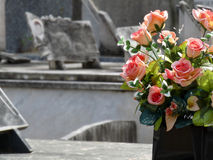Flowers on a gravestone. Pink roses on a gravestone Stock Image