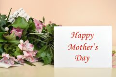Flowers and greeting card with Happy Mother's Day message. Bouquet of flowers and greeting card with Happy Mother's Day message. Selective focus royalty free stock photography