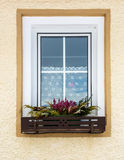Flowers growing under window in traditional Austrian house Stock Photo