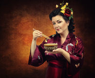 Flowers haired kimono woman eating with chopsticks Stock Photo