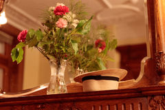 Flowers & Hat in Mirror of Elegant Home. Vase of flowers and straw hat on a mantle by a mirror stock photos