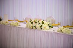 Flowers on the head table at a wedding. Flowers arranged at a head table at wedding Stock Photo