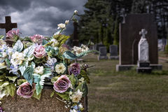 Flowers on a headstones in a cemetery. Bokeh effect in background Stock Image