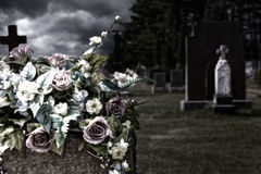 Flowers on a headstones in a cemetery. Bokeh effect in background Royalty Free Stock Photography