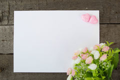 Flowers and heart shape note paper on wood background. Royalty Free Stock Photos