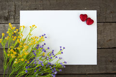 Flowers and heart shape note paper on wood background. Stock Photo