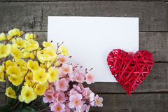 Flowers and heart shape note paper on wood background. Stock Photography