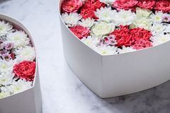 Gift box with heart shaped flowers on grey marble background royalty free stock image