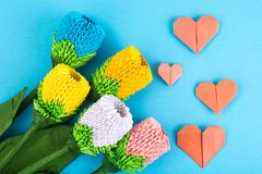 Flowers, hearts origami on blue background. Studio Photo Stock Images