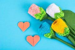 Flowers, hearts origami on blue background. Studio Photo Stock Photos