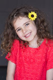 Flowers in her hair. Portrait of a young girl with a grey background. She is wearing casual clothing with a flower in her hair and smiling at the camera stock photography