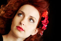 Flowers in her red hair. Beautiful woman on dark background with flowers in her vivid red hair. Shallow depth of field and focus on the eyes Stock Images