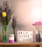 Flowers and home decorations set up with inspirational message 10. Lavander and colorful flowers in vase filled with coffee, candle and smile live and learn royalty free stock photos