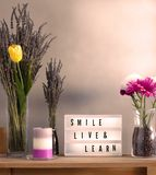 Flowers and home decorations set up with inspirational message 9. Lavander and colorful flowers in vase filled with coffee, candle and smile live and learn stock image