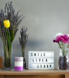 Flowers and home decorations set up with smile live and learn message board. Lavander and colorful flowers in vase filled with coffee, candle and smile live and royalty free stock image