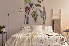 Flowers and a hummingbird painted on the fabric above a bed which is dressed in green plants pattern light color bedding in a cozy. Bedroom interior. Real photo royalty free stock photography