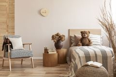 Free Flowers In Brown Vase On Wooden Nightstand Table Next To Single Bed With Stripped Bedding With Teddy Bear Stock Image - 156986411