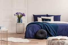 Free Flowers In Vase On Bedside Table Next To King Size Bed With Navy Blue Bedding Stock Photos - 152857823