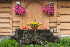 Flowers at an input in the wooden house.  Stock Photo