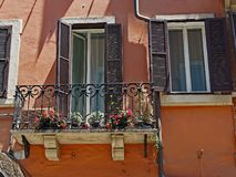 Flowers on Iron Lace Balcony, Rome, Italy. Colourful flowers in pots on a small iron lace balcony, with aged marble supports, on a traditional brown stucco Stock Photos