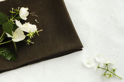 Flowers and jasmine petals on a linen napkin Stock Images