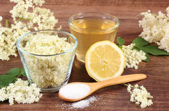 Flowers and juice of elderberry, ingredients for preparing beverage on rustic board Stock Photos