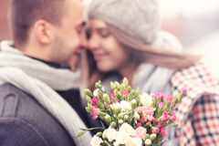 Flowers and kissing couple in the background Stock Image