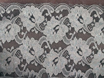 White flowers with pollen lace fabric pattern on dark brown wooden table background. Lacy embroidery for vintage style fashion clothing, tablecloth or curtain stock photography