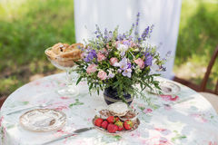 Flowers of lavender on the dining table outdoors. Dessert table for a party Royalty Free Stock Image