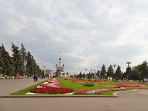 Flowers on the lawn and people walk. MOSCOW - September 2014: Palace with fountain, flowers on the lawn and the people strolling on the OCE, in September 2014 Royalty Free Stock Photography