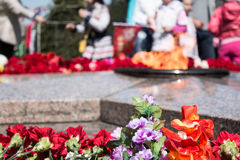 Flowers laying to the eternal flame. Memorial in honor of the fallen soldiers in the city of Omsk Russia Royalty Free Stock Photo