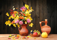 Flowers and leaves in a ceramic vase, fruit Stock Images