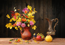 Flowers and leaves in a metal jug and fruit Stock Photography