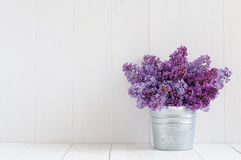 Flowers of lilac. Bouquet of beautiful spring flowers of lilac in a vase on a white vintage wooden board, home decor in a rustic style Stock Photo