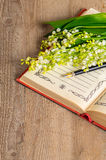 Flowers lily of the valley on the book for records and a pen Stock Images